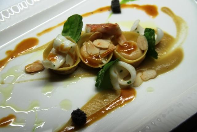 tortelli farciti di zuppa di pesce con crema di melanzane affumicate calamaretti a spillo mandorle salate foglie di spinaci e filetti di triglia