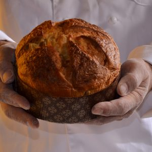 Cook holding panettone bread.